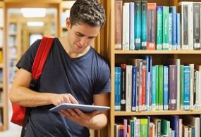 Student leaning against bookshelf holding a tablet pc at the library